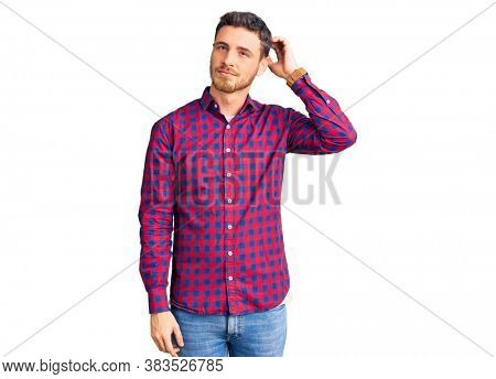 Handsome young man with bear wearing casual shirt confuse and wondering about question. uncertain with doubt, thinking with hand on head. pensive concept.