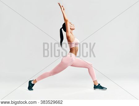 Young Sporty Woman Doing Yoga Asana Warrior I Pose On White Background. Practicing Yoga, Wellbeing A