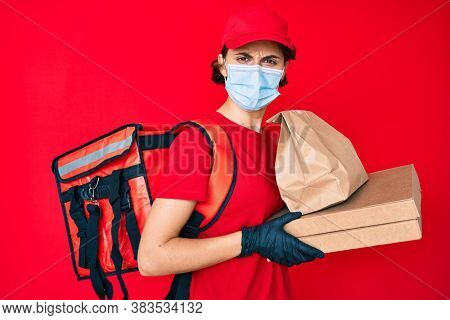 Young hispanic woman wearing medical mask holding take away food in shock face, looking skeptical and sarcastic, surprised with open mouth