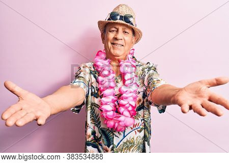 Senior handsome grey-haired man on vacation, wearing summer look with Hawaiian lei flowers looking at the camera smiling with open arms for hug. Cheerful expression embracing happiness.