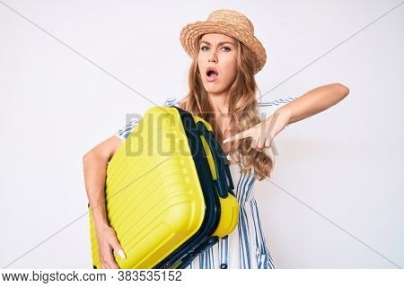Young caucasian woman with blond hair wearing summer dress and holding cabin bag in shock face, looking skeptical and sarcastic, surprised with open mouth