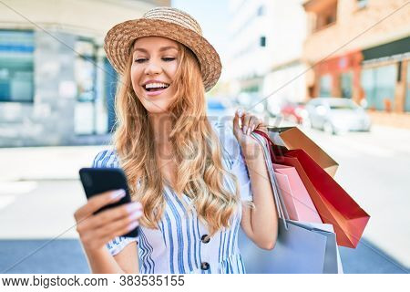 Young beautiful shopper woman smiling happy going to the shops sales holding shopping bags ourtdoors, smiling happy using smartphone