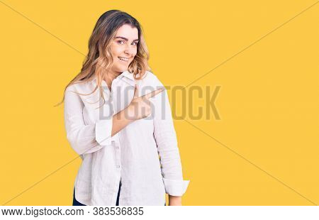 Young caucasian woman wearing casual clothes cheerful with a smile of face pointing with hand and finger up to the side with happy and natural expression on face