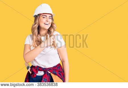 Young caucasian woman wearing security helmet cheerful with a smile of face pointing with hand and finger up to the side with happy and natural expression on face