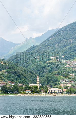 Landscape with Domaso City on Como Lake. High Mountains and Hills with Forest. The Church of Saint Bartholomew.