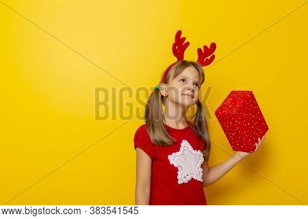 Beautiful Little Girl Wearing Deer Antlers Costume, Holding A Christmas Present Isolated On Yellow C