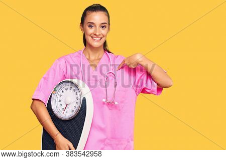 Young hispanic woman as nutritionist doctor holding weighing machine pointing finger to one self smiling happy and proud