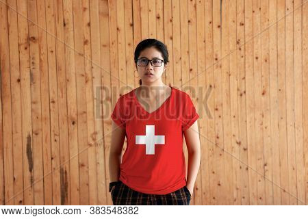 Woman Wearing Switzerland Flag Color Shirt And Standing With Two Hands In Pant Pockets On The Wooden