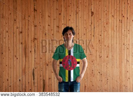 Man Wearing Dominica Flag Color Shirt And Standing With Two Hands In Pant Pockets On The Wooden Wall