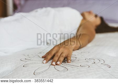 Woman Testing Mattress In Furniture Store. The Concept Of Filling A Mattress. Industry Concept.