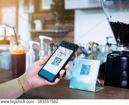 Customer Hand Using Smart Phone To Scan Qr Code Payment Tag  With Blurry Coffee Grinder In Coffee Sh