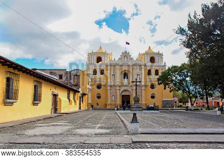 Iglesia De La Merced And Cobblestone Paved Plaza With Cross And Sky And Clouds, Antigua, Guatemala