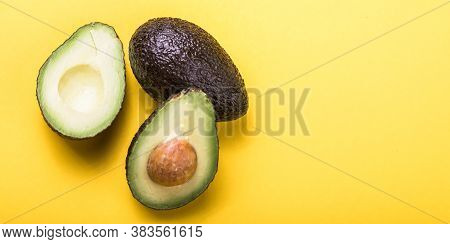 Two Haas Avocado Fruits On Yellow Colored  Background. Slice Avocado. Haas Avocado Fruits  On Yellow