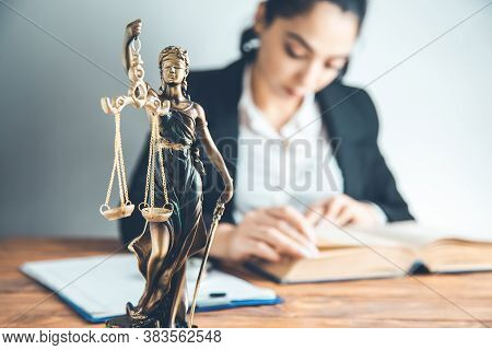 Woman Hand Book With  Justice Lady On Desk