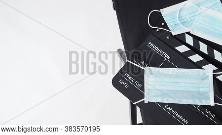 Director Chair And Black Clapper Board Or Movie Slate With Face Mask. It Use In Video Production And