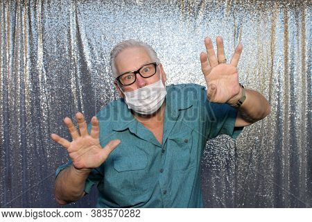 Photo Booth. A  Caucasian Man wears a Anti-Covid 19 Face Mask as he poses for photos in a Photo Booth with a silver sequin background.