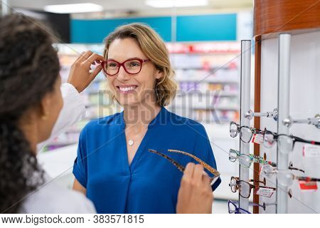 Mid adult woman in optic store buying new glasses. Happy smiling woman trying new eyeglasses with optician in pharmacy. Happy woman trying new spectacles frame in optic store.