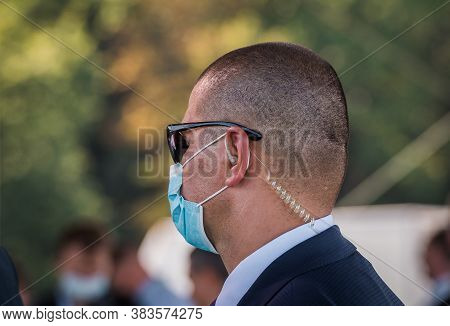 Security Guard Standing In Face Mask. Security Officer Bodyguard Standing And Listening Message With