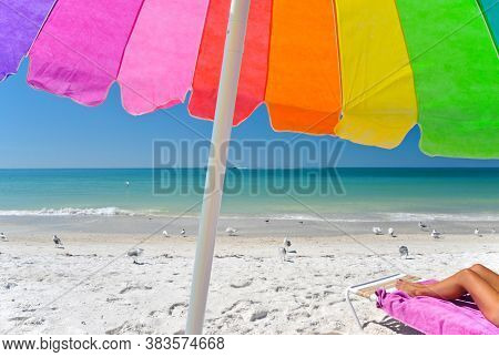 A Multi-clored Beach Umbrella With A Woman's Legs Showing On A Chair On The Beach While Enjoying The