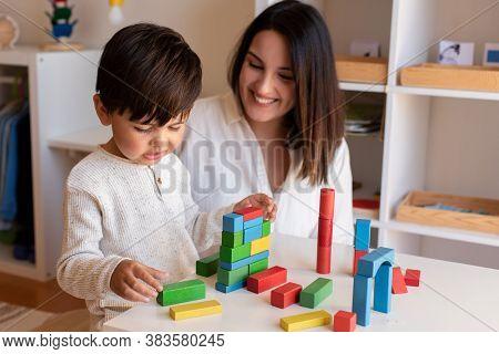 Liltle Preschooler Kid Playing With Wood Blocks And Teacher Educador Help. Homeshooling. Learning Co