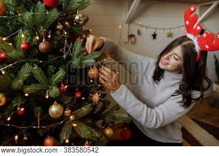 Stylish Young Woman Decorating Christmas Tree With Shiny Golden Bauble In Modern Room. Happy Girl In