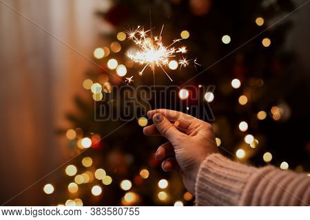 Happy New Year. Burning Sparkler In Hand On Background Of Golden Bokeh Lights In Festive Dark Room.