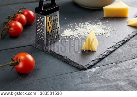 Piece And Grated Parmesan Cheese On Black Serving Board On Wooden Table With Cherry Tomatoes. Grated