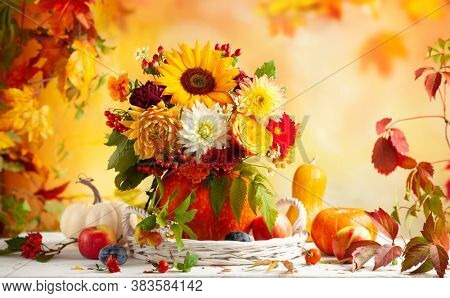 Autumn bouquet of beautiful flowers and berries in a pumpkin on wooden white table. Concept of autumn festive decoration for Thanksgiving day.