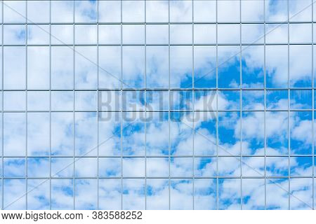 Reflection Of The Sky And Clouds In The Glass Wall Of A High-rise Building. Glass Wall Of A Skyscrap