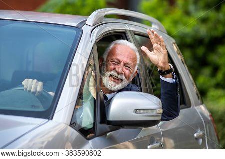 Happy Senior Man Waving Hand Through Window Of Gray Car