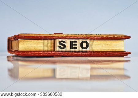 Seo Abbreviation, Search Engine Optimization Ranking Concept. Wooden Cubes With Notepad And Keywords