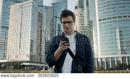 Young Man Walking In Moscow City With A Phone, Businessman Holding. Man On Background Of Business Ce