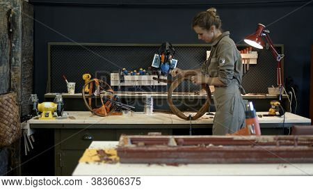 Restoration Of Wooden Chair In A Workshop. A Working Female Carpenter Peels Off Paint From A Wooden