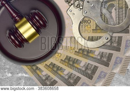 5 Euro Bills And Judge Hammer With Police Handcuffs On Court Desk. Concept Of Judicial Trial Or Brib