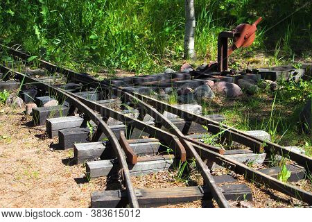 Narrow-gauge Railway In The Forest. Rails And Sleepers. Sleepers, Rails And Railway Arrow Close-up