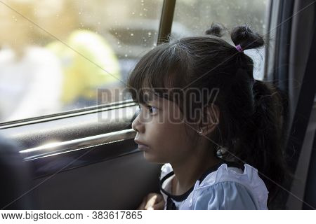 Asian Little Girl Looking Out Of The Car Window Wearily Due To Traffic Jams.