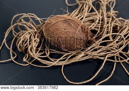 Coconut and coconut rope on black background