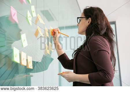 Confident Middle-aged Businesswoman Writing On Sticker With Pencil And Brainstorming. Colorful Memo