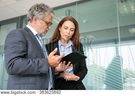 Grey-haired Boss Discussing With Assistant, Holding Tablet And Standing In Conference Room. Beautifu