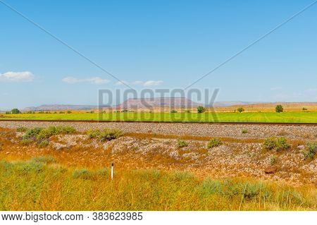 Flat Plains Of New Mexico With Distant Flat-top Mesa Landform In Distance And Railway Tracks Through