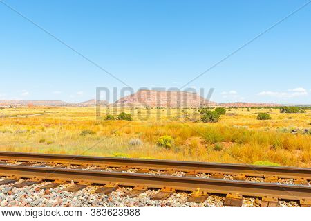 Railway Tracks Across Flat Plains Of New Mexico With Distant Mesa Landforms Under Blue Sky.