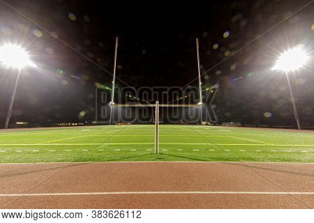Empty American Football Stadium At Night Illuminated