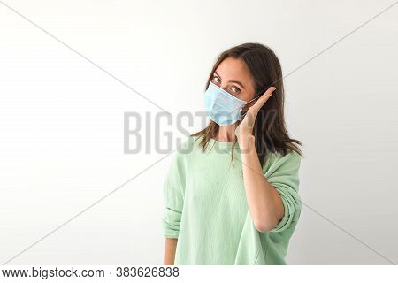 Adult Female In Medical Mask Keeping Palm Near Ear And Looking At Camera While Pretending To Make Ca