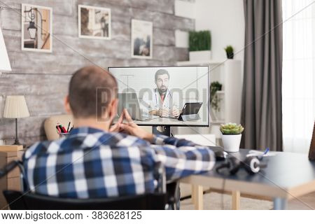 Man With Walking Disability In Wheelchair Talking With His Doctor On Video Call. Young Immobilized G