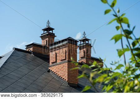 A Small Red Brick House With A Beautiful Copper Roof And Chimneys Against A Clear Sky.