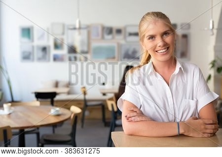 Happy Beautiful Blonde Woman Wearing White Shirt, Standing In Co-working Space, Leaning On Desk, Pos