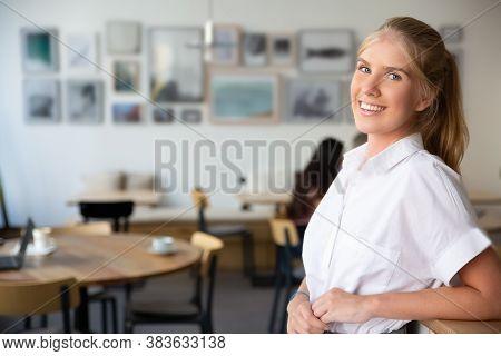 Joyful Beautiful Blonde Woman Wearing White Shirt, Standing In Co-working Space, Leaning On Desk, Po