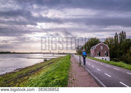 Middleaged Man Walking Along River Waal Near Zaltbommel In The Netherlands