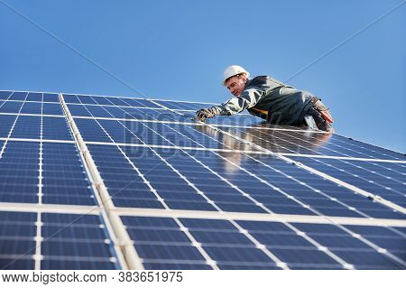Side View Of Male Worker Installing Solar Modules And Support Structures Of Photovoltaic Solar Array