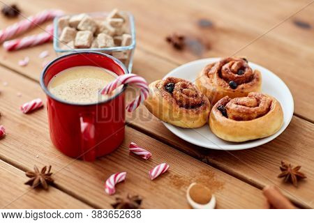 christmas and seasonal drinks concept - eggnog in red cup with candy cane decoration, cinnamon buns and aromatic spices on wooden background